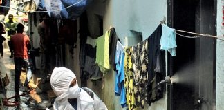 A worker wearing a protective suit disinfects a slum area as a preventive measure against the spread of coronavirus outbreak, in Mumbai. (ANI Photo)