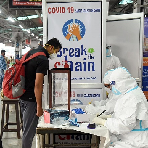 A passenger stands as sampling and testing are taking place for the coronavirus at the Jammu railway station, in Jammu (ANI Photo)