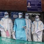 Health Workers wearing protective suit as they receive a COVID-19 patient at LNJP hospital in New Delhi. (ANI Photo)