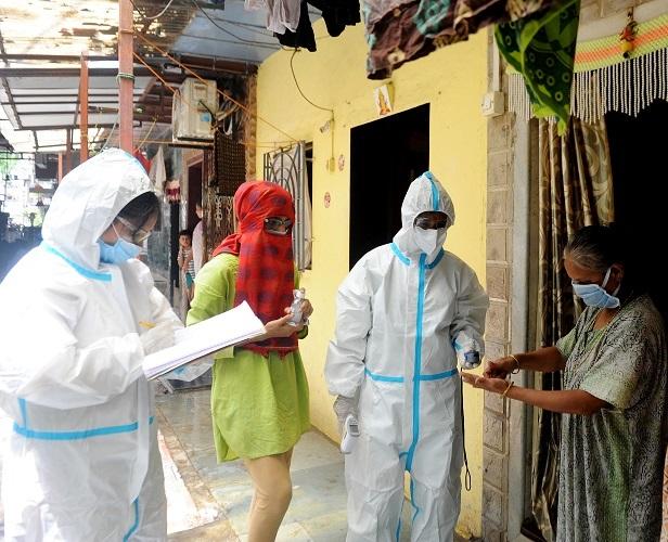 Healthcare workers doing door to door check-up of COVID-19 test of the Bail Bazaar, Kurla slum area, in Mumbai on Tuesday. (ANI Photo)